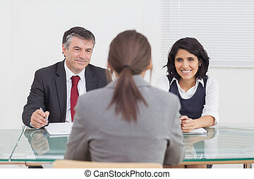 Business people talking and smiling in a small meeting in...