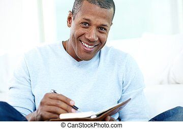 Male student - Image of young African man writing something...