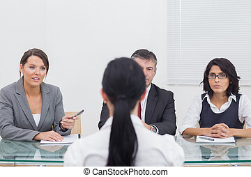 Three business people folding hands in small meeting...