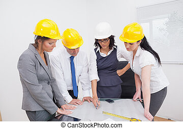 Team looking at a construction plan in office