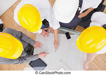 Team looking at a construction plan with hard hats in office