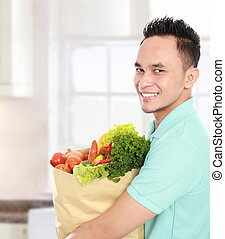 Man with a grocery bag - Portrait of smiling young man...