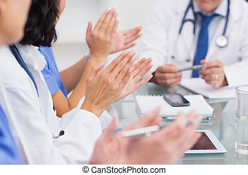 Nurses clapping a doctor during meeting