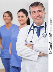 Doctor with arms crossed and his team of nurses smiling