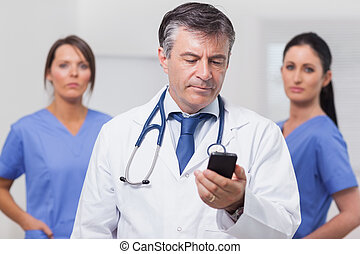 Doctor looking at phone with his team of nurses in the...