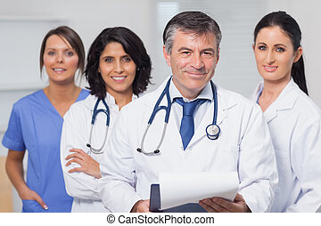 Doctor holding clipboard with his team on the background
