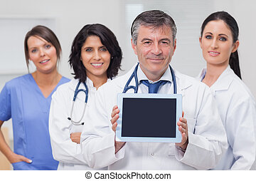 Doctor showing tablet pc with his team behind him