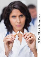 Doctor breaking cigarette in two