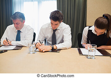 Business people taking notes at desk during meeting