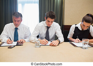 Business people in a meeting taking notes