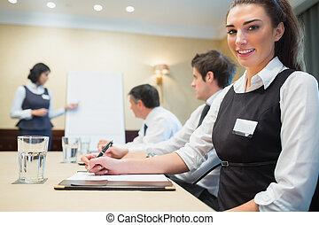 Smiling businesswoman during a presentation in conference...