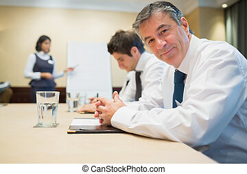 Smiling businessman during meeting in conference room