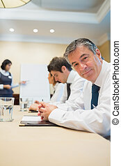 Happy businessman at presentation in conference room