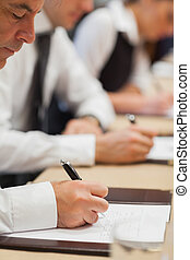 Businessman making notes during meeting