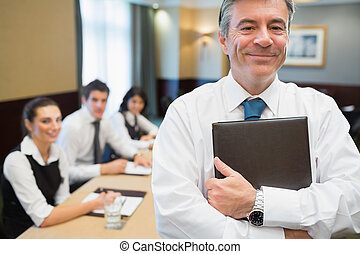 Businessman holding folder at conference standing and...