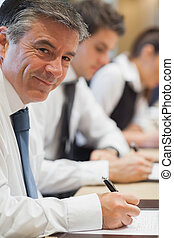 Happy businessman taking notes during conference
