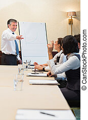 Smiling man pointing during presentation in conference room