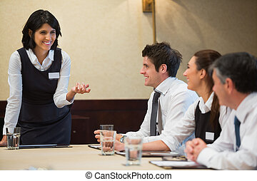 Businesswoman talking to team in conference room