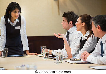 Woman asking question in business meeting in conference room
