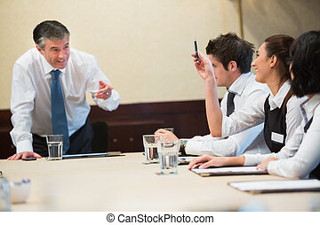 Woman asking question in a business meeting in a conference...