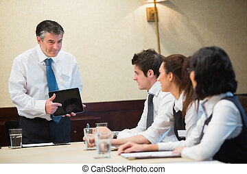 Businessman using tablet in meeting in conference room