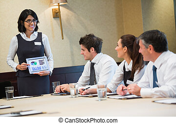 Businesswoman using tablet during presentation