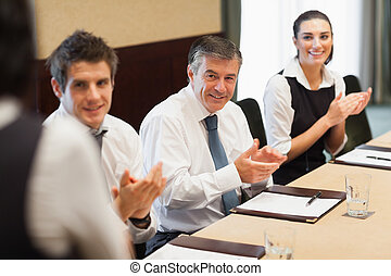 Business people clapping after a presentation in conference...