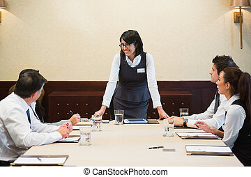 Happy businesswoman standing at head of table in conference...