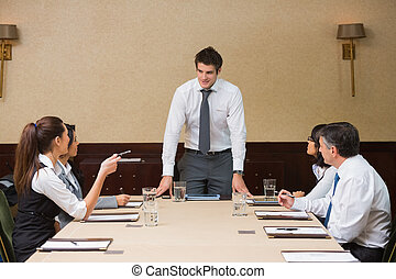 Businessman standing at head of table in conference room