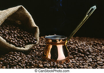A Turkish coffee pot with beans and a sack