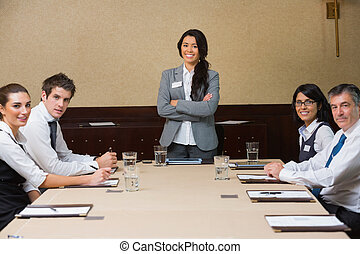 Smiling woman at head of business meeting in conference room