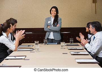 Businesswoman being applauded by peers in conference room