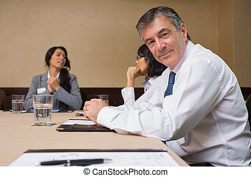 Happy businessman at meeting in conference room