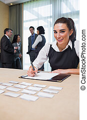 Happy woman at welcome desk at business conference