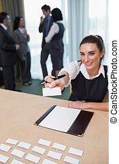 Woman handing you a name tag at business conference