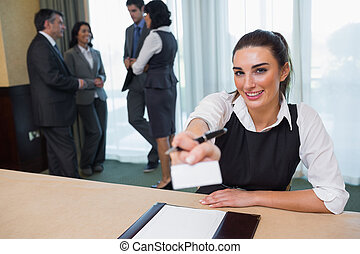 Happy woman handing you a name tag at business conference