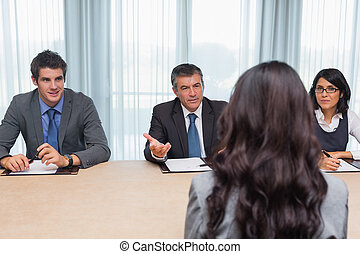 Interviewer asking woman a question before a business panel