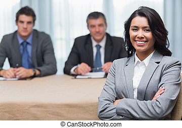Smiling woman with interview panel in conference room