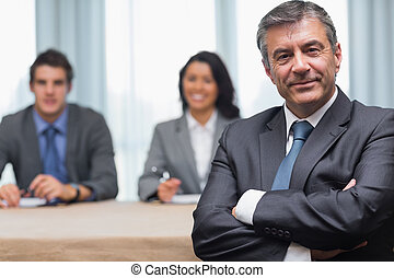 Businessman with arms crossed sitting with business panel in...