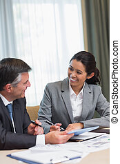 Business people happily talking during meeting