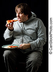 Overweight man eating a pizza.