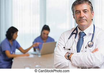 Doctor standing with arms crossed during meeting