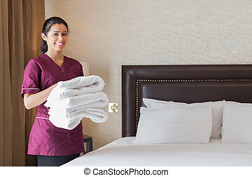 Hotel maid holding pile of fresh towels in hotel room