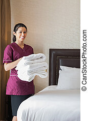 Smiling hotel maid holding towels in hotel room