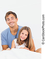 Father and daughter on the bed smiling