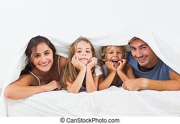 Family in the duvet smiling