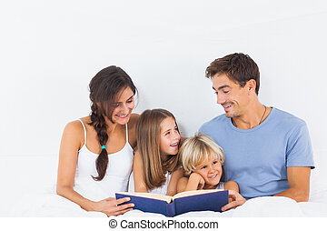 Family sitting with a book on the bed in the bedroom