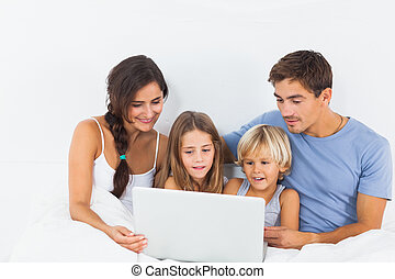 Family sitting with a laptop on the bed