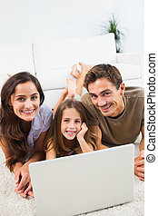 Smiling family lying on a carpet with the laptop in the...