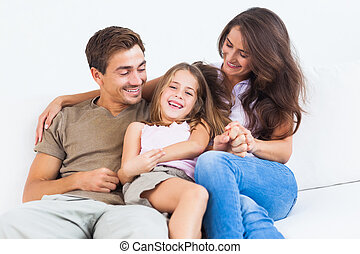 Smiling family playing together on a sofa in the living room